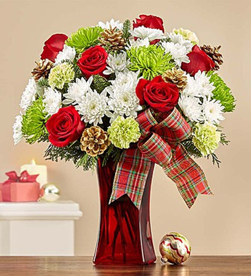 Our enchanting bouquet of roses, carnations, poms and greens accented by whimsical gold pinecones delivers all the magic and wonder of the holiday season—no sleigh required! Hand-designed by our expert florists in a vibrant ruby red gathering vase adorned with a fun and festive plaid ribbon, it's a delightful arrangement guaranteed to leave all the special people in your life feeling merry and bright.
