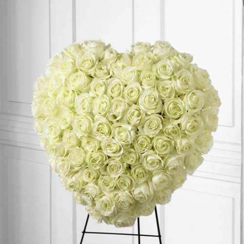 "The FTD® Elegant Remembrance™ Standing Heart is an exquisite display of peace and love. 77 Stems of white roses are artfully arranged in the shape of a heart and presented on a wire easel, creating a simply beautiful tribute for their final farewell service. Approximately 24""H x 22""W."