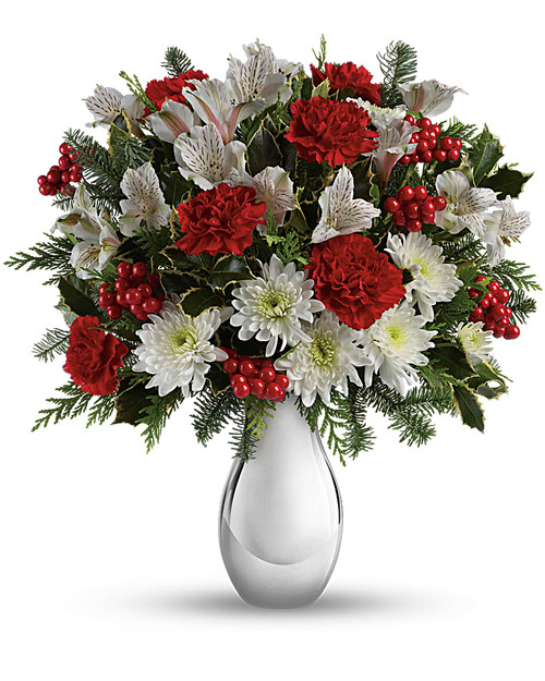 Pure winter wonder! Crimson carnations and red berries bring a festive touch to the snowy blooms of this lush holiday bouquet. Our magnificent silver vase makes this a gift to remember! Red carnations, white alstroemeria and white cushion chrysanthemums are arranged with variegated holly, flat cedar, noble fir and red berries.  Delivered in Teleflora's exclusive Silver Reflections vase or similar. Orientation: All-Around