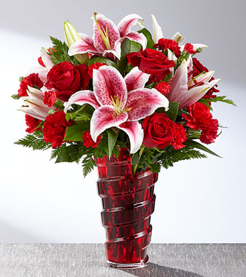 The FTD® Lasting Romance® Bouquet is ready to make your special someone's heart skip a beat this coming February 14th! Stunning Stargazer Lilies are set to catch the eye with their soft fragrance and fuchsia and white bi-colored petals, arranged amongst rich red roses, red carnations, and red mini carnations with lush green accents. Presented in a keepsake red glass vase with a spiral design starting at the base and looping up to the top to give it a modern styling they will love, this gorgeous Valentine's Day flower bouquet is the perfect way to express your heart's every wish.
