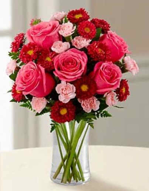 The Precious Heart Bouquet by FTD® is a blushing display of loving kindness. Fuchsia roses are sweetly stunning amongst red matsumoto asters, pink mini carnations and lush greens. Arranged in a classic clear glass vase, this bouquet boasts pink perfection to convey your warmest wishes.