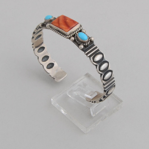 Slender sterling silver cuff with some very nice stamp and reposse work and turquoise and orange spiny oyster shell.