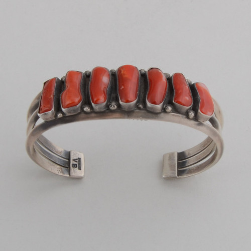 Sterling silver cuff with open work on the sides, holding beautiful, natural red coral.