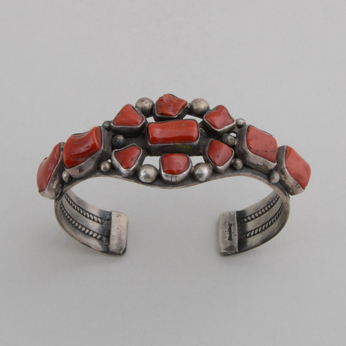 "Sterling silver cuff with natural red coral forming a ""daisy""."