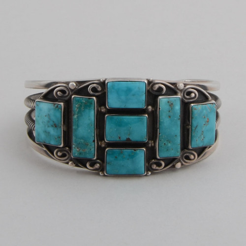 "Sterling silver cuff with open work on the sides and ""curls"" around the turquoise stones."