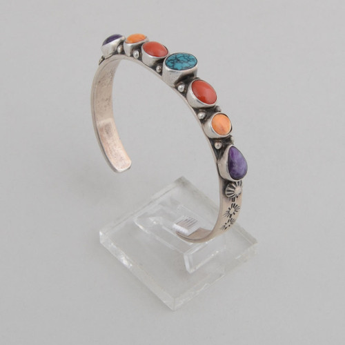Slender stamped sterling silver cuff with spiderweb Turquoise, coral, orange spiny oyster shell and sugilite.