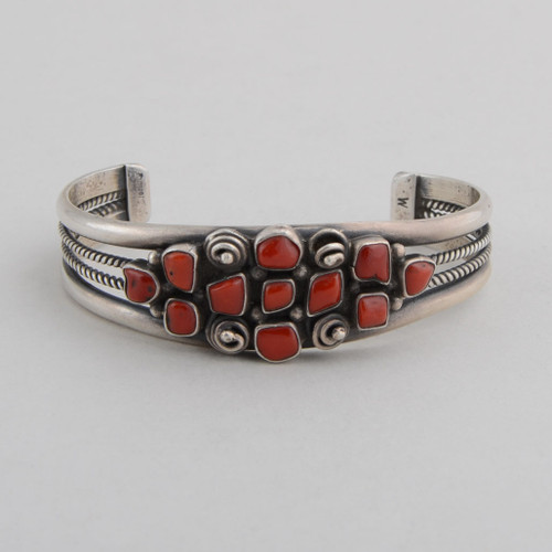 Sterling silver cuff with open rope work on sides, red coral with silver rosettes on top.