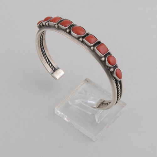 "Slender sterling  silver cuff with ""rope"" work on the sides and red coral across the top."