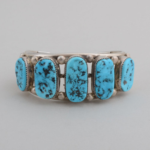 Bold sterling silver cuff with open work on the sides and large nugget Turquoise stones.