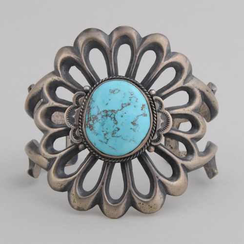 A beautiful sandcast cuff bracelet surrounds a wonderful Kingman Turquoise stone by Harrison Bitsui.