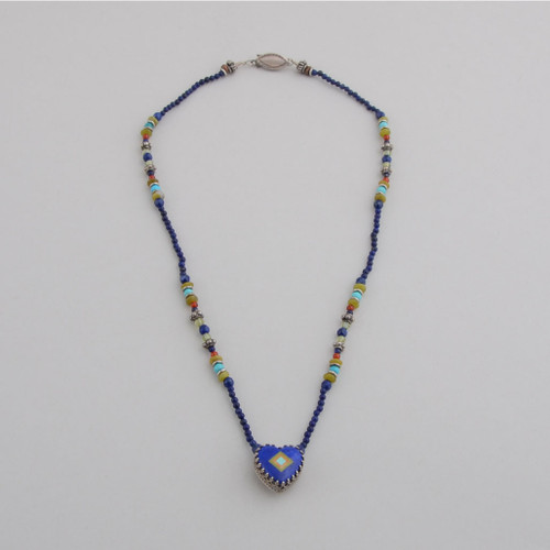 Delicate inlaid lalpis lazuli heart on beads.