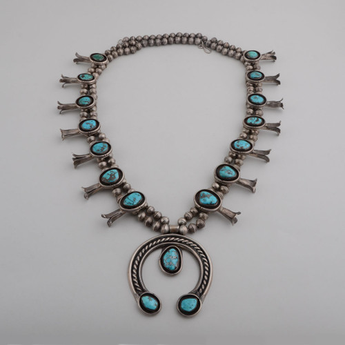Beautiful 1950s vintage squash blossom necklace featuring handmade beads, Morenci Turquoise and sterling silver!  The shadow-box style of the squash blossoms and Naja really set the Morenci turquoise off!