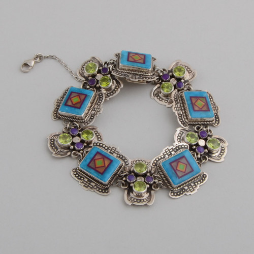 Inlaid link bracelet with peridot and sugilite between links.