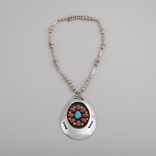 A classical shadowbox style pendant, with turquoise and coral.