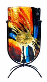 The face of the vase, showing the gold splatter central, with yellow, orange, and reds, coming out of center with blues on a black setting. The colors are almost astronomical.