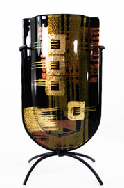 Face of this powerful, mini-vase. Made of fused glass and featuring a versatile but strong color palette and design, this piece can accommodate a variety of interiors, though more masculine, dark colors, black, and darker hardwoods are among the more natural fits for this piece.
