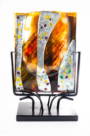 Shown here in front view, the vase imparts its coloration to the light penetrating its translucent composition resulting in a tawny, autumn dawn light cast gently all about the piece.