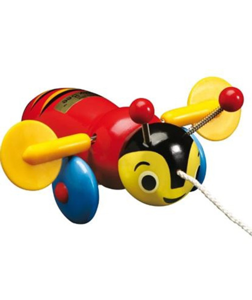 """Buzzy Bee Pull Along Toy Buzzy Bee is an iconic pull-along toy, recognised by most New Zealanders as it has been around for children to enjoy for more than 50 years. As it is pulled by its string the spinning wings and wheels go round and round and it makes a """"clicking noise"""" which gets louder as you go faster. Mostly made of wood and painted with non-toxic paint."""