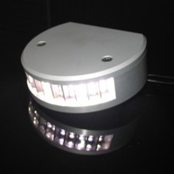 a black reflective background with a silver round light base at an angle. Super white light in the middle