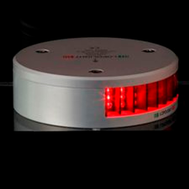 A black background with a round light base. Glowing red light on half. Right side