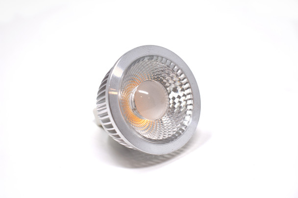 A small round Kuma DMS LED Dimmable GU10 COB . Silver outside. Clear lens. A bulb on the inside. On a white background