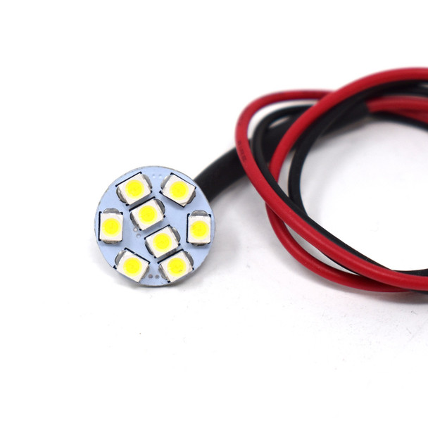 A small Emma 8SMD. Round with yellow square lights on the inside. Wires attached. On a white background
