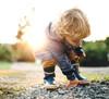 child picking up rocks