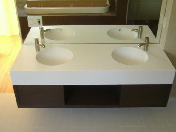 Custom floating vanity with DuPont Corian top and custom Corian bowls.