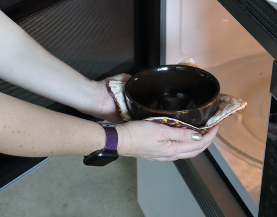 Bowl Cozy being pulled from a microwave.