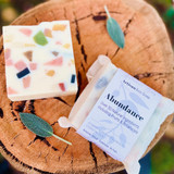 A hand made eco soap with over 50 natural ingredients in a coconut milk base. Scented with essential oils, this bar will nourish your skin and uplift your body and mind. You can also use to scent clothes by slipping underneath garments or hang in a cupboard. Your soaps can be cut in half for longer use - one for scenting linen and the other for your skin.