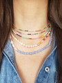Woman Wearing Colorful Necklace Layers. Top Necklace is Gold Choker with Rainbow CZ Stones. Second Necklace is Silver Choker with Rainbow CZ Stones. Third Layer is a Dainty Beaded Adjustable Necklace with Rainbow Seed Beads. Fourth Layer is a Split Necklace with White Pearls on One Half and Colorful Thick Seed Beads with Gold Link. Bottom Layer is a Split Necklace with Half White Shell Pearls and Half Blue and White Glass Beads with Gold Accent. | Mojo Supply Co