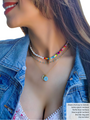 Woman Wearing Saskia Layer is a Split Necklace with White Pearls on One Half and Colorful Thick Seed Beads with Gold Link Layered with Gold Dainty Necklace and Blue Initial and Dog Paw Charm