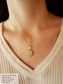 Two Dainty Layered and Styled Necklaces on Body in Cream Sweater. Top Necklace is Dainty Gold Link Chain with Small Moon and Star Celestial Necklace Pendant Charm. Bottom Necklace is Dainty Gold Link Chain with Tiny White Opal Connector and Round Gold Swirl Textured Pendant with Small White Opal Stone Center | Mojo Supply Co