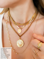 Woman Wearing Gold Necklaces Including Ebba Stainless Steel Choker, Astrid Snake Chain Necklace With Zora Oval Coin Pendant, Elise Thick Gold NecklaceWith Cadence Greek Pendant And Kaiya Long Rosary Beaded Chain Necklace   Mojo Supply Co