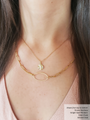 Woman in Pink Top with Brown Hair Wearing Two Layered Gold Necklaces. Top Necklace is a Dainty Gold Chain with a Dainty Gold Medallion Pendant with a White Opal Center Stone. Bottom Necklace is a Custom Made Gold Paperclip Link Chain with Gold Oval Pendant Connector | Mojo Supply Co