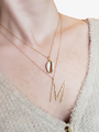 Woman Wearing Layering Sloane Necklaces Accentuated With Marjorie Letter M Pendant And Cindy Cowrie Shell Charm | Mojo Supply Co