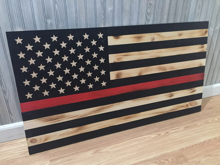 Shown Inside against a wall: Thin Red Line wood flag 24 x 13 inches, carved stars on union. Firefighter flag