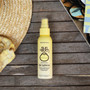 Lifestyle shot for Sun Bum Hair Lightener. Yellow Fade to White bottle on a grey timber deck with the edge of a beach hat in the top left corner.