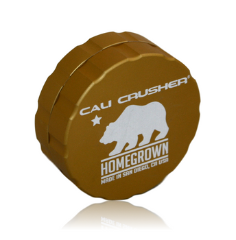 """Cali Crusher's *PREMIUM* Lineup! Homegrown! 2-Piece 'Pollenator' 2.35"""" Gold Model.  Grooved edge for easy grip. Ultrasonically cleansed 6061-T6 Aerospace Medical Grade Aluminum Patented radial cut blades for maximum shredding: cuts one way, fluffs the other. New blade layout allows for a larger loading capacity. Neodymium rare earth magnets for superior closure, easily hold the grinder from the lid. Blades/Teeth covered under a lifetime warranty!"""