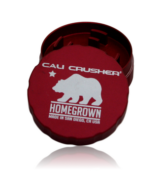 """Cali Crusher's *PREMIUM* Lineup! Homegrown! 2-Piece 'Pollenator' 2.35"""" Red Model.  Grooved edge for easy grip. Ultrasonically cleansed 6061-T6 Aerospace Medical Grade Aluminum Patented radial cut blades for maximum shredding: cuts one way, fluffs the other. New blade layout allows for a larger loading capacity. Neodymium rare earth magnets for superior closure, easily hold the grinder from the lid. Blades/Teeth covered under a lifetime warranty!"""