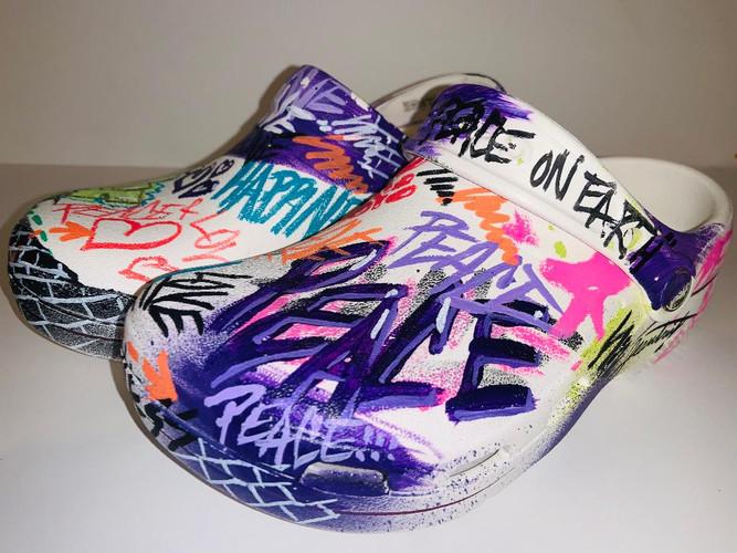 White graffiti tagged Peace + Love Crocs (women's)