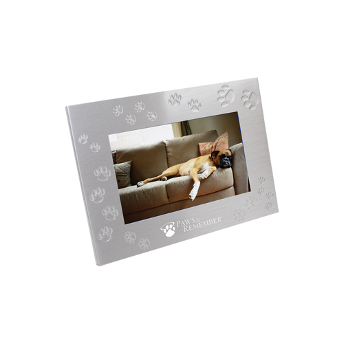 """Brushed aluminum with black felt backing and glass front. Has a 4"""" x 6"""" photo frame with debossed paw prints."""