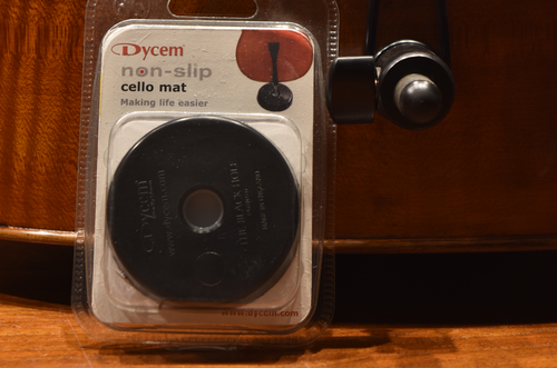 Dycem Cello Endpin Stopper in package next to cello endpin for scale reference
