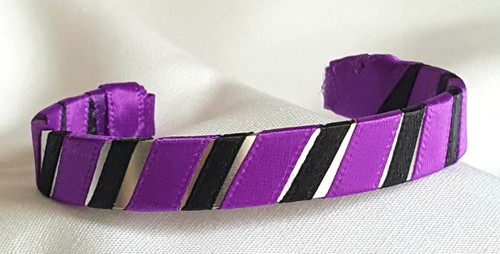 Show off your School Colors by wearing our Black and Purple Ribbon Cuff Bracelet.  Aluminum base with creatively decorative wrapped ribbon.  Perfect for individual inspiration, school groups/events, donation requests and for whatever your creative imagination brings.