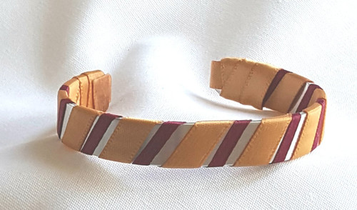 Show off your School Colors by wearing our Gold and Maroon Ribbon Cuff Bracelet.  Aluminum base with creatively decorative wrapped ribbon.  Perfect for individual inspiration, school groups/events, donation requests and for whatever your creative imagination brings.