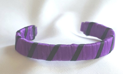 Show off your School Colors by wearing our Purple and Black Ribbon Cuff Bracelet.  Aluminum base with creatively decorative wrapped ribbon.  Perfect for individual inspiration, school groups/events, donation requests and for whatever your creative imagination brings.