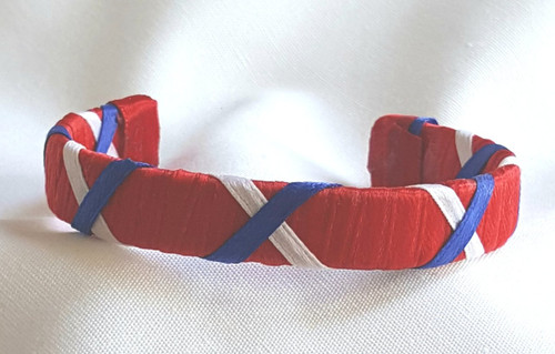 Show off your Proud to be an American by wearing our Red White and Blue Ribbon Cuff Bracelet.  Aluminum base with creatively decorative wrapped ribbon.  Perfect for individual inspiration, school groups/events, donation requests and for whatever your creative imagination brings.