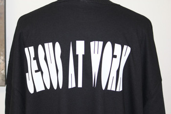 Jesus at work on the back our a black shirt.