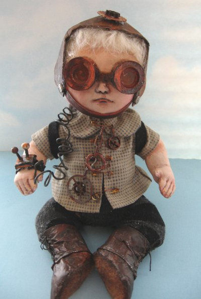 """Steampunk Baby - Sitting 8"""" tall this amazing baby is wearing tyvek hat and shoes, pants made from socks and a variety of embellishments made from paperclay."""