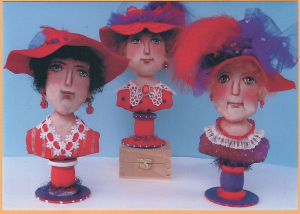 """These zesty 8"""" painted muslin Red Hat Ladies are perched on wooden spools."""